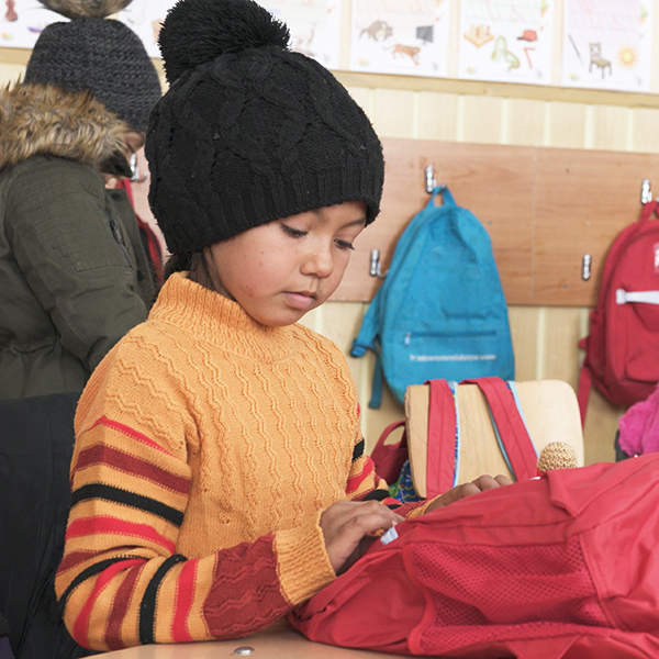 Romanian orphan looking in his new school bag